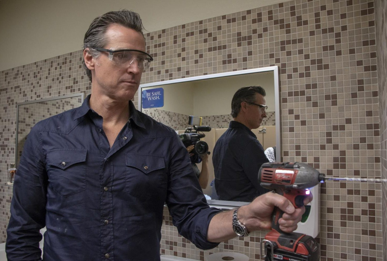 Governor Gavin Newsom assist Maria Arambula with replacing the paper towel dispenser at American River College during International Workers' Day on May 1, 2019. (Photo by Ashley Hayes-Stone)