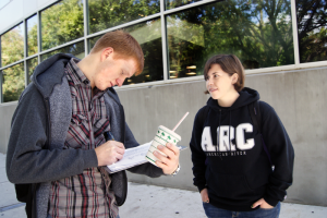 Kate Clark watches 18-year-old music major Igor Vnydyuk sign her petition to make American River College a smoke-free campus on Tuesday, Oct. 5, 2011. (Photo by Shanel Royal)