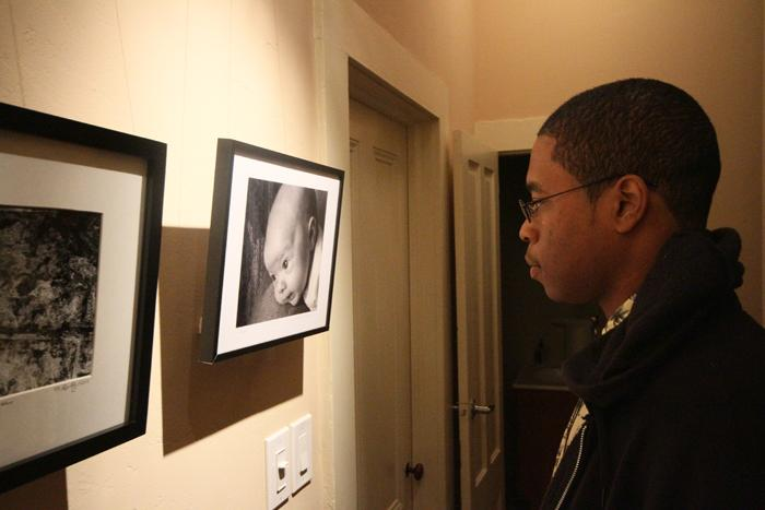 Gavin McIntyre, a student with art in the show, examines another student's photo on Feb. 11 at the Union Hall Gallery in downtown Sacramento. (Photo by Daniel Romandia)