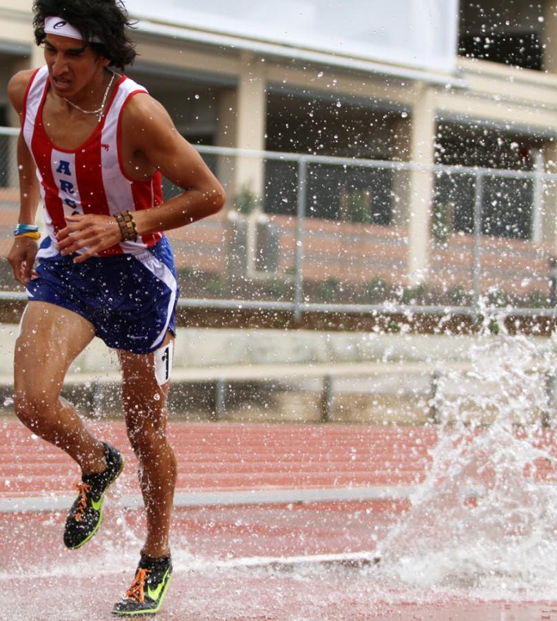 Luis Luna running in the steeplechase race at American River College on Apr 6. He is ranked third in the state in this event. (Photo by Daniel Romandia)
