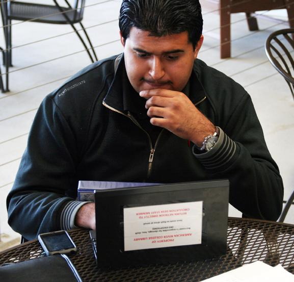 ARC student Victor Villarreal, biology major, using the library's laptop to do his anthropology class homework. Laptops at the library are available for check out for two hours at a time.