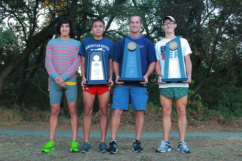 From left to right: Sophomores Luis Luna, Will Reyes, head coach Rick Anderson and sophomore Jacob Huston hold the three state championships the team has won (2005, 2011, 2012). (Photo by Emily K. Rabasto)