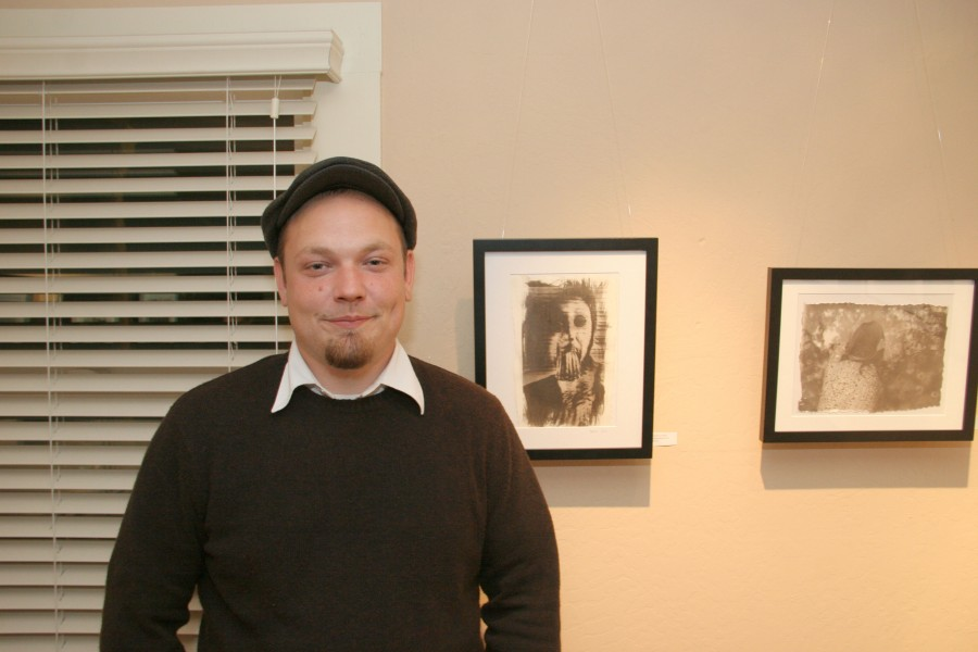 """Photography major Tysen Cannady next to his artwork titled """"Impending Doom"""" at the exhibit on K street"""