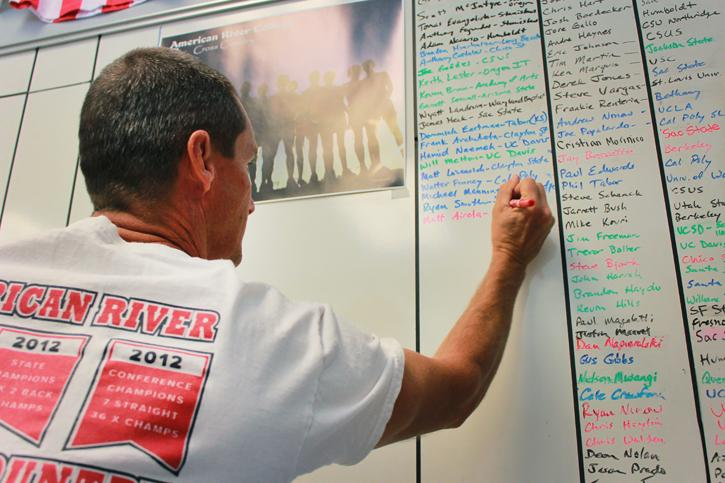 Cross-country coach Rick Anderson writes his team;s current running statistics on a whiteboard located in his office, which provides a visual motivation for the members of his squad. Anderson's method of recording data is considered more straight-forward compared to other advanced statistics. (Photo by Emily K. Rabasto)