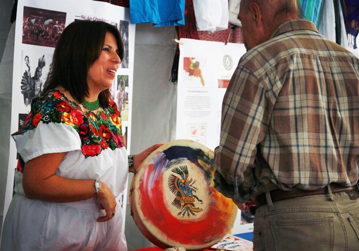 Lisa Aguilera Lawrenson, Associate Vice President of Instruction at American River College, explains the history behind a Nisqually Indian drum to a visitor of Sacramento World Fest. The drum is made of stretched elk skin and cedar wood and was given to her as a gift from her father. (Photo by Emily K. Rabasto)
