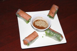 "Roses on the Grill Rolls, flavorful and fragrant spring rolls served with a peanut dipping sauce, are prepared with a grilled vegetarian ""sausage"" instead of the more traditional shrimp."