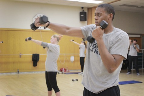 Using two hand weights, Cleveland Braswell executes rotating punches during a three-part circuit workout during the Boot Camp Fitness class at American River College. (Photo by Emily K. Rabasto)