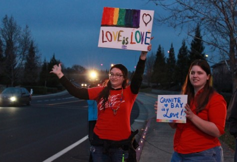 Current and former presidents of ARC Fierce Lydian Countryman, left, and Kindra Pring, right, hold up homemade signs outside of Granite Bay High School on Thursday night in support of the school's newest drama production,