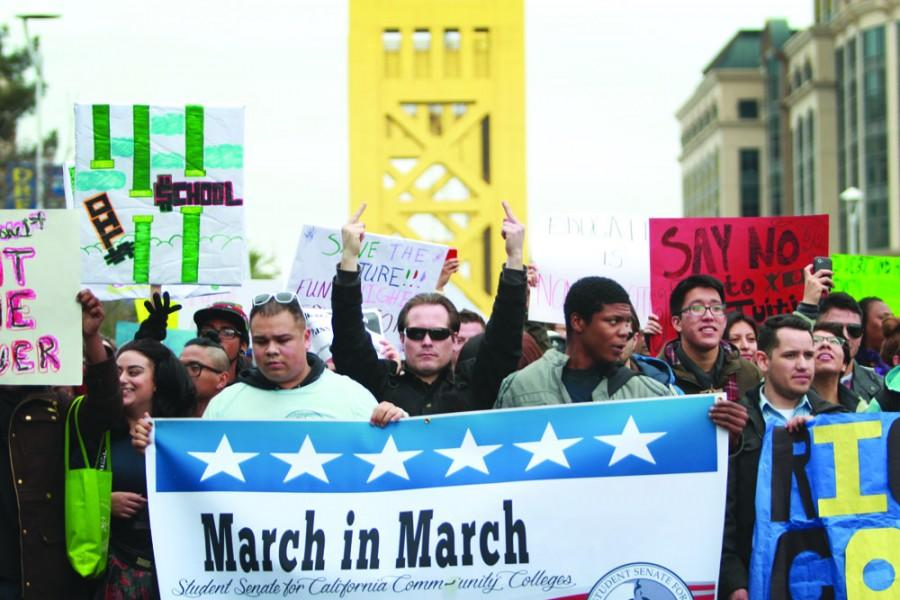 Leading the march, Keith Montes of Diablo Valley College raises his middle fingers