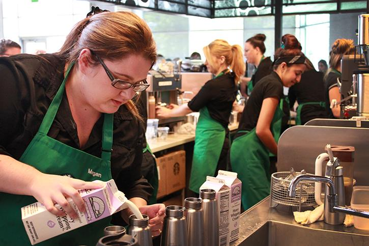 Starbucks barista Megan Doering, 24, quickly fills canisters with whipping cream to accommodate the intimidatingly long line of customers waiting to order their drinks.  Doering has worked at the American River College campus Starbucks for two years and says that it is busier than the others she has worked at. (Photo by Emily Rabasto)