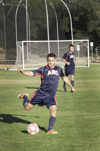 Julio Vizcarra a midfielder kicks the ball to a teammate downfield.