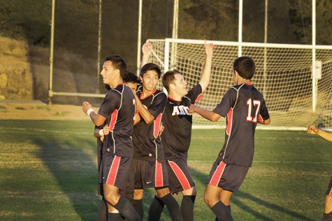 The men's soccer team celebrates after scoring the only point of the game, which resulted in their first win of the season.