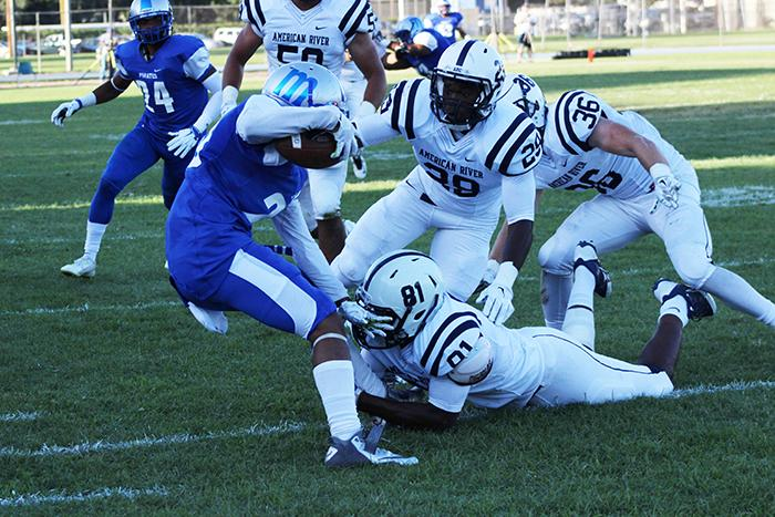 Modesto Junior College defensive back Lesean Collins is tackled by American River College wide receiver Malik Dumetz after intercepting a pass from ARC qaurterback Chris Guillen during the season opener on Sept. 5, 2015. ARC blamed the loss on  a poor week of practice. (Photo by Barbara Harvey)