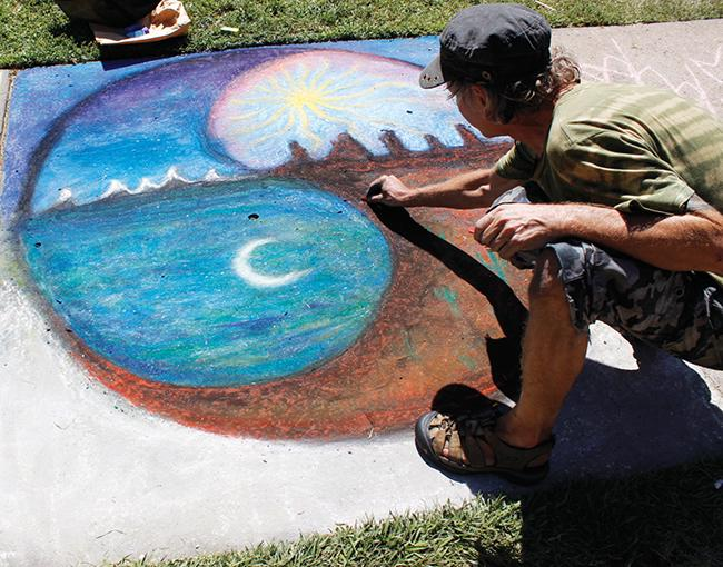 John Steensland, a former American River College student, adds finishing touches to his  chalk-drawing for Chalk It Up. He said he liked the way the texture of his art looked on the pavement. (Photo by Cheyenne Drury)