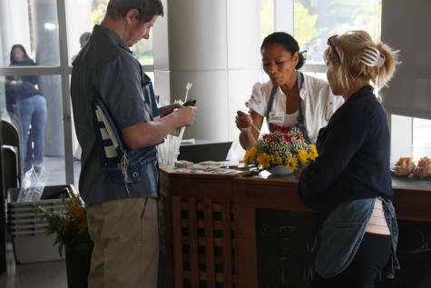 Ryan Nix, a health services assistant at American River College, is purchasing flowers at American River College's floral sale on Sep. 17 as Jamie Decoudreaux and Dira Zavolokina explain how to take care of them. (Photo by Jose Garcia)