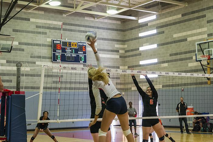 American River College setter Monica Udahl smacks the ball over the net as two Lassen players stretch out to defend the play. ARC won the second game of the match 25-12 on Aug 28, 2015. (Photo by Joe Padilla)