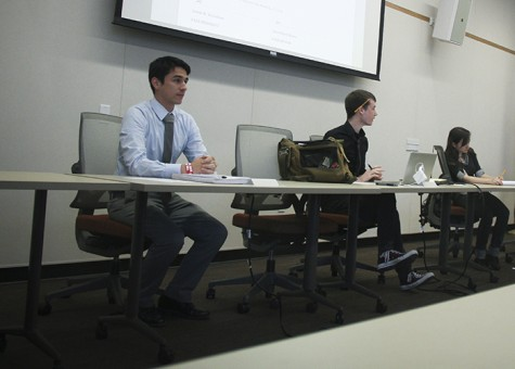 ASB Student Senate President Garret Kegel, left, Clubs and Events Board President Justin Nicholson and CAEB Vice President Mary Stedman go over the agenda during the CAEB meeting Tuesday. The board discussed changes to bus routes and briefly addressed last week's shooting at Sacramento City College. (Photo by Jordan Schauberger)