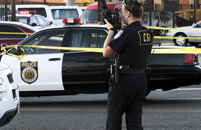 A crime scene investigator takes pictures of the aftermath at Sacramento City College on Thursday after a shooting that left one student dead and two others injured.