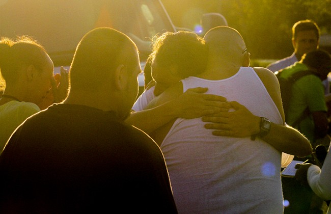 Bystanders hug outside of Sacramento City College Thursday after the on campus shooting that left one student dead and two others injured.