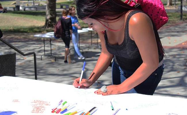 Sacramento City College student Lenora Tigner signs the condolences poster at the love-in held on Sept. 4, the day after a fatal shooting occurred on the Sacramento City College campus. Tigner, like many others at the love-in, expressed shock over the first ever shooting at a Los Rios school. (Photo by Barbara Harvey)