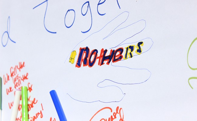 "Geve Spooner, who says he was close friends with Sacramento City College shooting victim Roman Gonzalez, drew an outline of his hand signed ""Brothers"" on a condolences poster at the love-in at Sacramento City College on Sept. 4, 2015. Spooner said that his family has been close to Gonzalez's family for generations. (Photo by Barbara Harvey)"