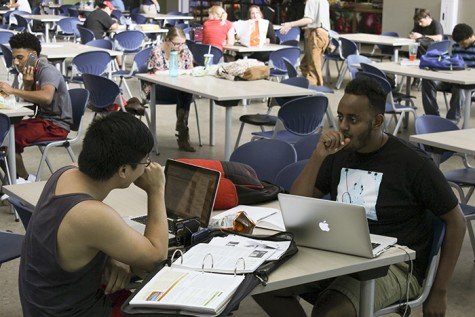 American River College student Brian Wong, left, works on homework in the Student Center with his friend Israel Solomon, a UC Riverside alum who visited Wong on campus. Wong said that he only uses the WiFi in certain areas of the campus. (Photo by John Ferrannini)