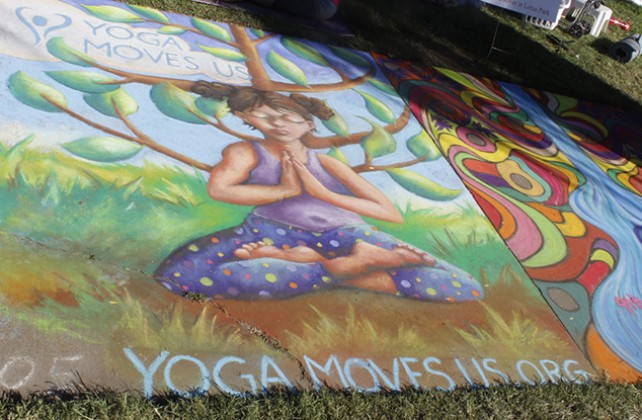 A chalk advertisement for Yogamovesus.org at Chalk It Up's 25th annual art festival on Labor Day weekend in Fremont park, downtown Sacramento. There were a lot of chalk advertisements for local businesses at the event. (Photo by Cheyenne Drury)