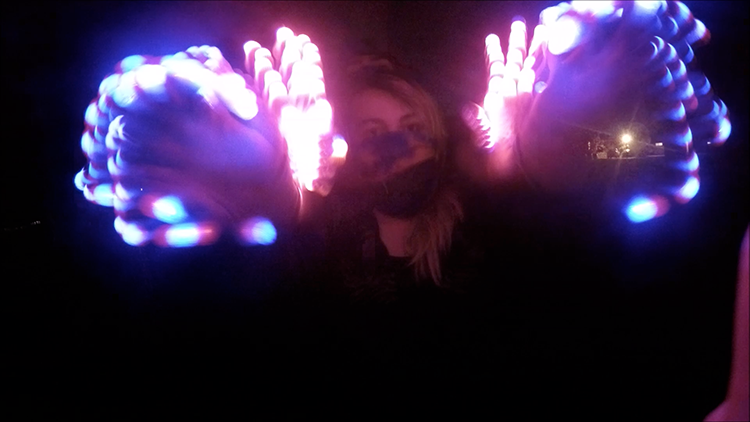 This screenshot shows American River College students Anthony Perez and Vanessa Lamb perform a light show with gloves that are outfitted with LED lights. This type of performance has been associated with the electronic dance music scene. (Image capture of a video by Lena DoBynes)
