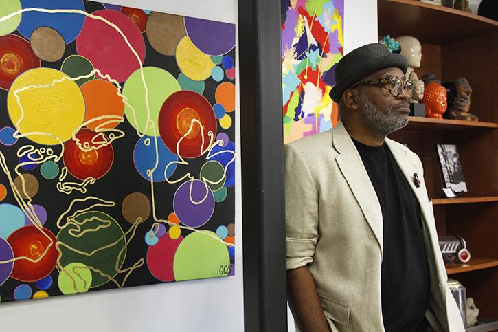 "Former ARC professor Gerry Otis Simpson, also known as GOS"", stands before his piece ""Pop Culture Icon Float Like A Butterfly,"" a portrait of Muhammad Ali which recently came back from display at the Muhammad Ali Center in Louisville, Kentucky. Simpson said he only ever began painting as a way to decorate his walls cheaply, but he's made waves in the art world with his pop art paintings."