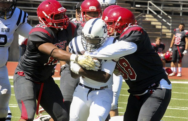 American River College running back Armand Shyne attempts to get away from a group of City College of San Francisco players during his team's game against CCSF of Sat. Sept. 26. Arc won the game with a score of 20-17 . (Photo by Ashlynn Johnson)