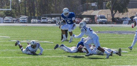 College of San Mateo slot receiver David Rango leaps over his own player before being tackled by American River College safety Robert Sanders during ARC's 42-10 loss to CSM on Oct. 3, 2015. CSM ran for 298 yards against ARC's defense. (photo by Joe Padilla)