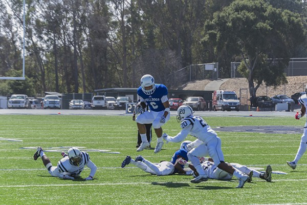 College of San Mateo wide receiver David Rango leaps over his own player before being tackled by American River College defensive back Robert Sanders of American River College on Oct. 3 2015 at San Mateo. CSM won the game 42-10. (photo by Joe Padilla)