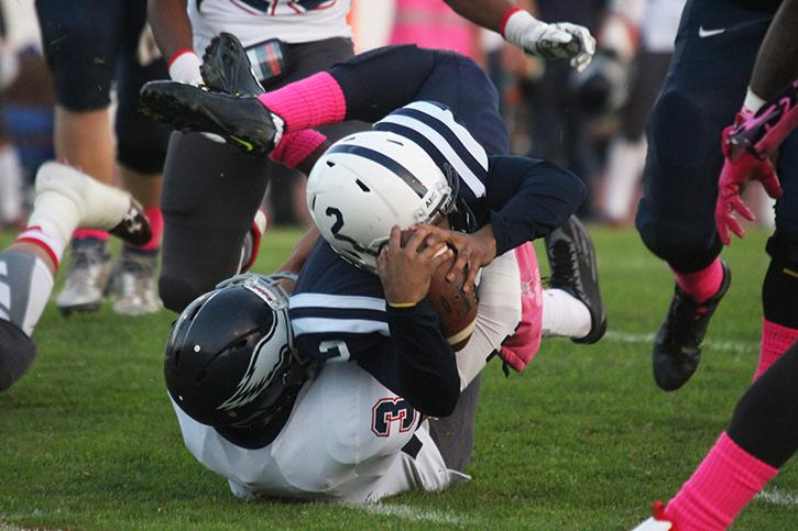 American River College quarterback Jihad Vercher is brought down on a quaterback keeper by College of the Siskiyous defensive back Everette Deveaux during ARC football's 49-31 win over College of the Siskiyous on Saturday, Oct. 18, 2015. Vercher threw for 230 yards and 2 touchdowns in addition to his one rushing touchdown. (Photo by Barbara Harvey)