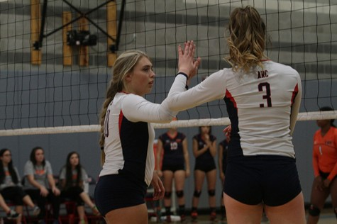 "Kaitlin Meyer slaps the hand of teammate Nora Troppmann during American River College's match against Cosumnes on Oct. 21, 2015. Meyer said Troppmann is ""one of my best friends."" (Photo by Nicholas Corey)"