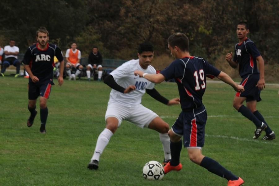 American River College defender Francisco Lomeli (19) attempts to move the ball past a Modesto Junior Collge defender during ARC's 1-0 win over MJC on Oct. 27, 2015. With the win, ARC's overall record stands at 5-10-3. (phtoto by Kevin Sheridan)