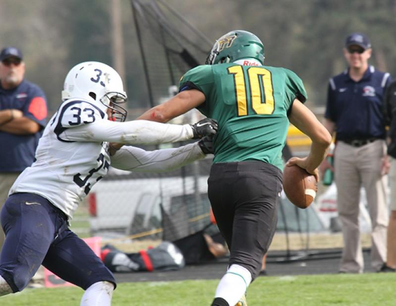 American River College defensive back Bryce Kasch grabs the jersey of Feather River's quarterback George Barajas on October 24, 2015. Kasch ended the game with two tackles in the 44-14 victory for ARC. (Photo by Nicholas Corey)