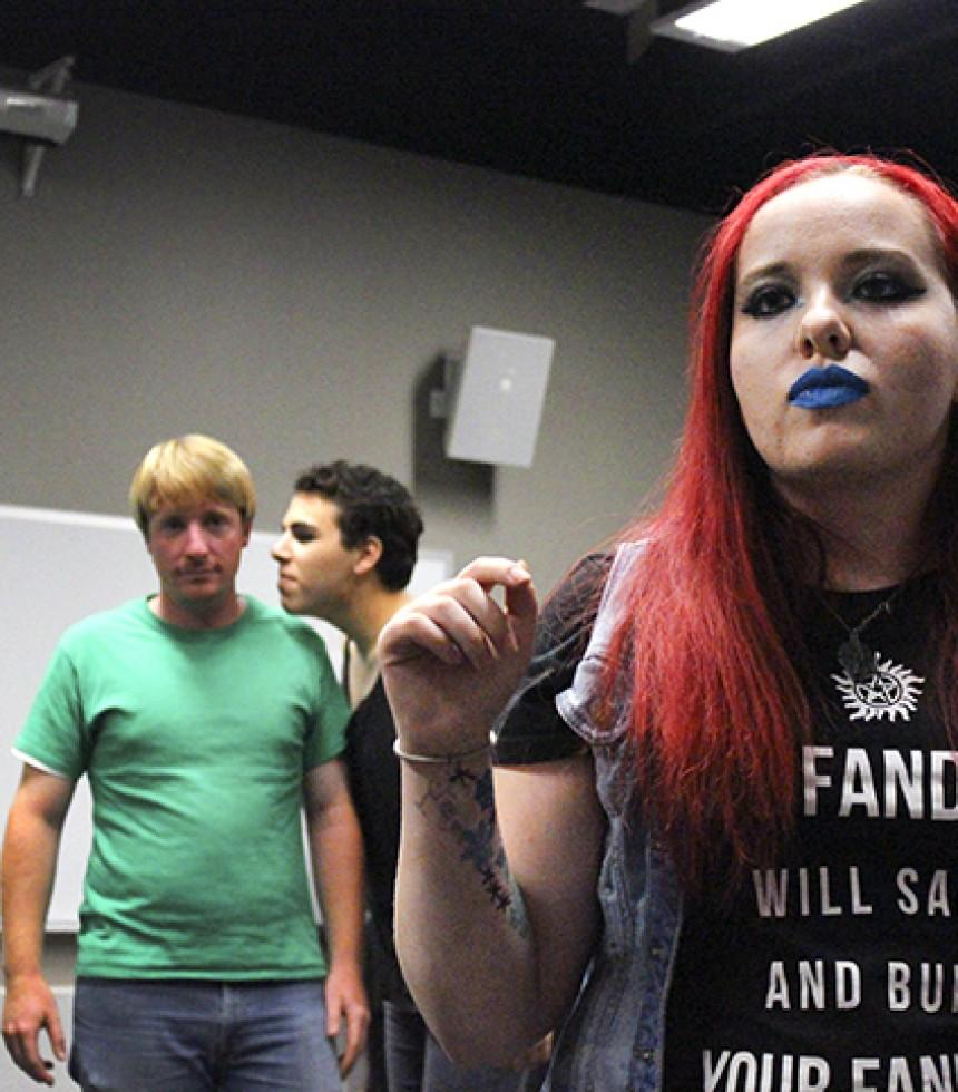 Kori Einsel, who is in charge of public relations for the American River College Improv club, searches the crowd for volunteers during the punk rocked themed late night meeting the club held on Thursday, Sept. 24. (Photo by Ashlynn Johnson)