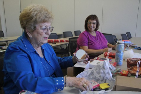 Sondra Fuson, left, and Ellen Read wrap items to be sold at the
