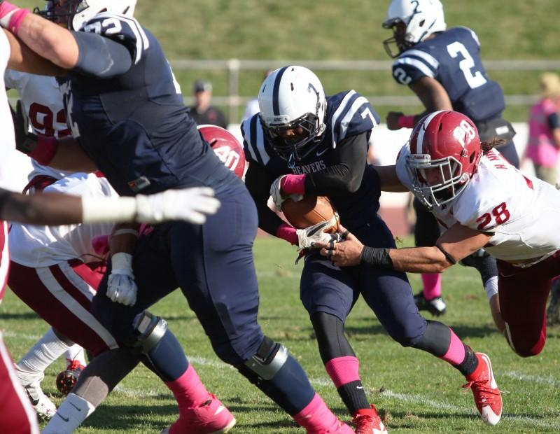 American River College running back Austin Hines rushes the ball for 9 yards before being brought down by Sierra College linebacker Hank Humphers during ARC's 47-22 victory over rival Sierra on Saturday, Oct. 31, 2015. (Photo by Barbara Harvey)