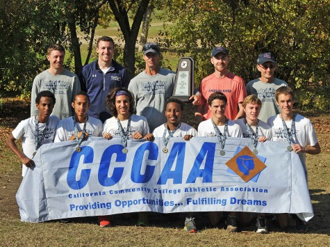 ARC's State Championship winning cross-country team and coaching staff hold up the CCCAA banner and show off their medals. ARC won the State Championship for the fourth time in five seasons with a score of 67.