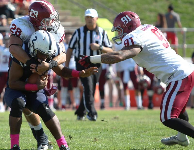 American River College quarterback Jihad Vercher is brought down by Sierra College lineback Hank Humphers and defensive lineman Vinnie Consentino during ARC football's 47-22 win over rival Sierra on Saturday, Oct. 31, 2015. (Photo by Barbara Harvey)