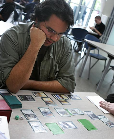 American River College student Casey Reynolds plays the card game 'Magic: The Gathering' with friends in the Student Center. Tabletop games can be a good way to teach skills and knowledge to students. (Photo by Ashlynn Johnson)