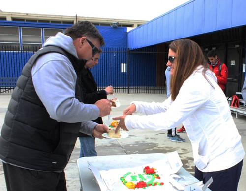 Water polo coaches Eric Black (left) and Bethani Black (right) eating cake for Eric's birthday on the American River College pool deck. (Photo by Noor Abasi)