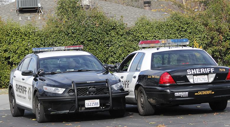 Two Sheriff's Department cars sit outside of the Sacramento Metro Fire District Station near College Oak Drive and Saddlerock Way. Police are searching for a man who they allege to have hit a California Highway Patrol car using a stolen vehicle. (Photo by Jordan Schauberger)