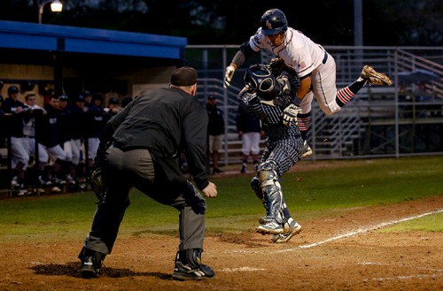 ARC outfielder Justin Jordan flies through the air while being tagged at home by the West Valley College catcher on Jan.28, 2016 at American River College in Sacramento Calif.The game was ARC's season opener, hosing West Valley College where ARC ended up losing 7-6. (Photo by Kyle Elsasser)