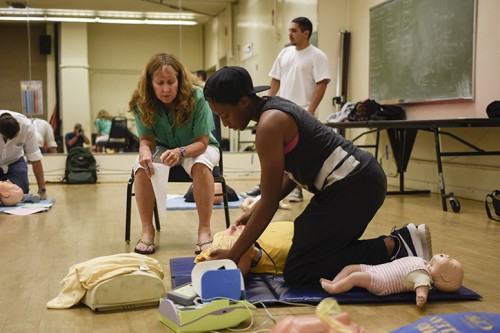Professor Joanne English provides CPR/AED training to ARC student Alexis Holt in the main gym. Two classes yet to start in the spring 2016 semester will offer AED and CPR training. (Photo by Tracy Mapes)