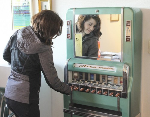 Abbey Cocreham demonstrates use of the Art-O-Matic art dispenser at the Kaneko Gallery at American River College in Sacramento, California on Feb. 18. The Art-O-Matic reopened this semester to raise money for the gallery. (Photo by Hannah Darden)