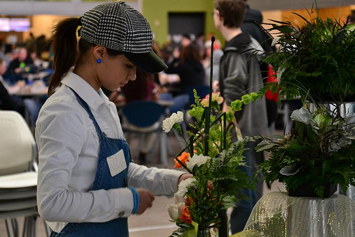 American River third year intern Nina Railean arranges a floral display for sale at the American River College student center Feb. 4, 2016. (Photo by Joe Padilla)