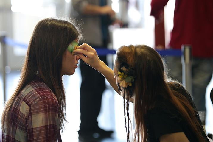 Makeup artists paint the faces of audience members before seeing American River College students perform in the production Gumbo. Gumbo is a theatrical variety show with a theme of
