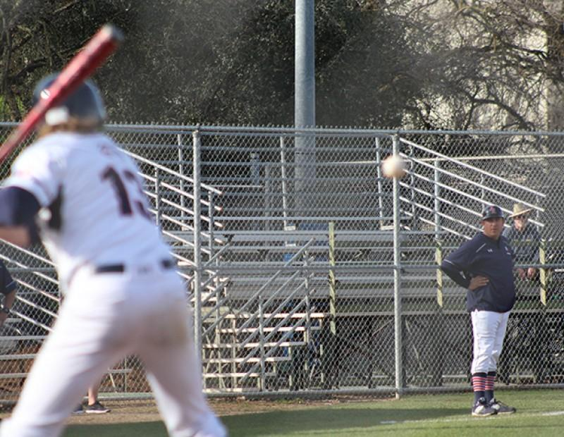 American River College coach Doug Jumelet looks on as 3B Brayden Gomez swings at a ball against Solano College. ARC lost 6-5. (Photo by Mack Ervin III)